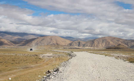 View of the mountains and dramatic sky on the gravel road to Everest Base Camp, Tibet, China photo