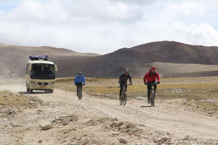 A tourist bus and a group of cyclists from the Everest Base Camp Mountain Bike Tour on the gravel road in Tibet, China
