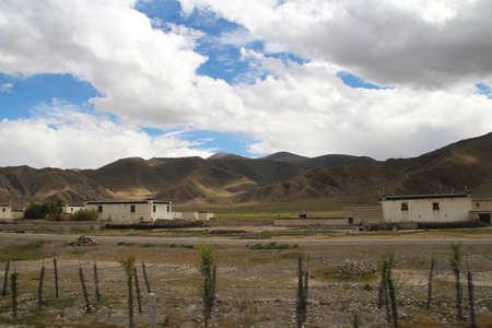 tibetan house: View of the mountains and Tibetan house with dramatic sky in Tibet, China
