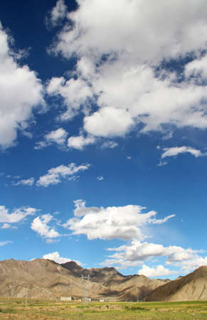 View of the mountain and Tibetan village with dramatic sky in Tibet, China Stock Photo