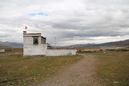 tibetan house: Tibetan house with the dirt road in a cloudy day, Tibet, China