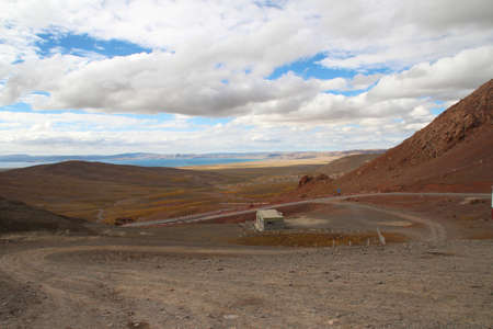 View of mountains, dirt road and Namtso Lake with the dramatic sky in Tibet, China