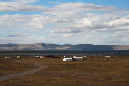 nomadic: View of mountains, grassland, Nomadic tents and Namtso Lake with the dramatic sky in Tibet, China