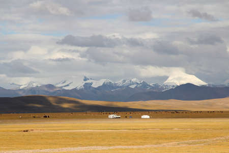 nomadic: View of Tanggula Mountains, grassland, Nomadic tents with the dramatic sky near Namtso in Tibet, China Stock Photo