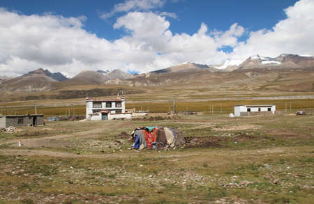View of ice mountains, Tibetan house and  Qinghai Tibet Railway track with the dramatic sky in Tibet, China