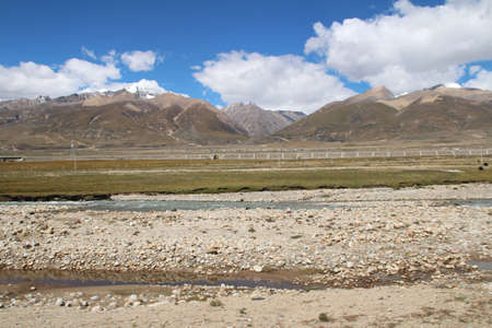 railway track: View of ice mountains QinghaiTibet Railway track and stream with the dramatic sky in Tibet China
