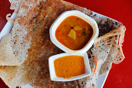 dosa: Rava dosa or Ravvattu or Rave Dose is an Indian crepe of South India serve with curry and chilli sauce
