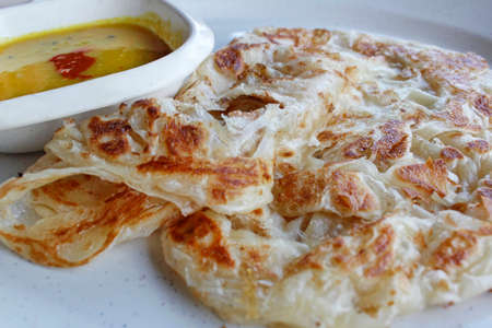 clarified: Roti canai or pan fried flatbread consisting of dough egg ghee and serve with the curry sauce Stock Photo