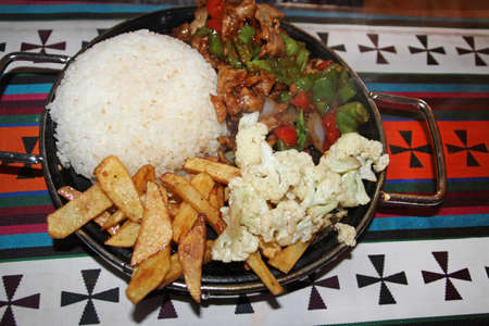 rice plate: A meal with pork stir-fry, fried potatoes, cauliflower and rice in Tibet, China