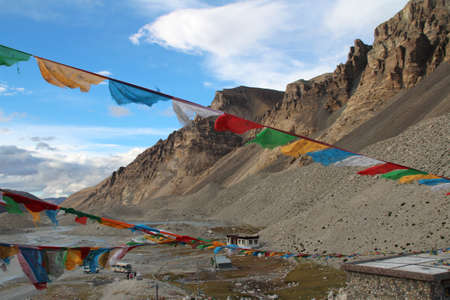 sutra: View of mountains with the sutra streamers, bus and tourist at Everest Base Camp, Tibet. Editorial