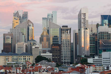 south asian ethnicity: View of Singapores Chinatown with red rooftop of shop houses and citys financial district and skyscrapers as background in sunset