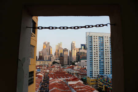 southeast asian ethnicity: Chain link as frame in blur across Singapores Chinatown with red rooftop of shop houses and citys financial district and skyscrapers as background in sunset Editorial
