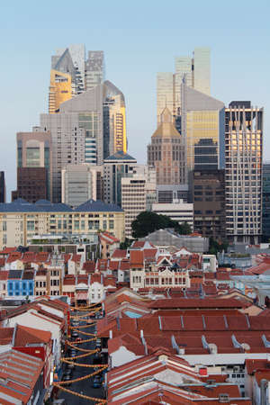View of Singapores Chinatown with red rooftop of shop houses and citys financial district and skyscrapers as background in sunset