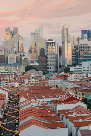 southeast asian ethnicity: View of Singapores Chinatown with red rooftop of shop houses and citys financial district and skyscrapers as background in sunset