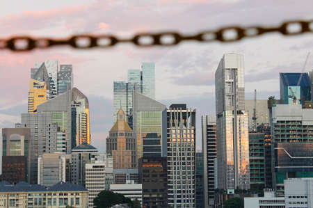 southeast asian ethnicity: Chain link as blur foreground across Singapore skyline from Chinatown in sunset