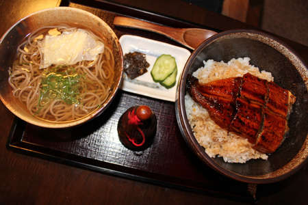 saltwater eel: Unagi Kabayaki, eel grilled on rice and soba noodles and some pickles in a set meal at Japanese restaurant in Kyoto, Japan Stock Photo