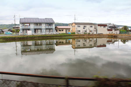 View of a rural town with the pond of reflection along the way to Nara, Japan