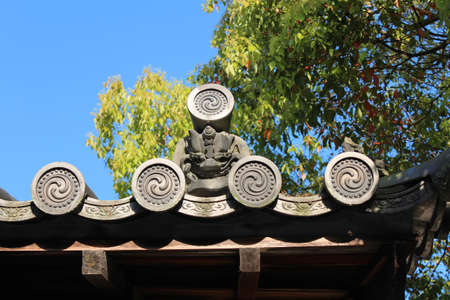 Oni are a kind of yokai from Japanese folklore. Oni-faced roof tiles called onigawara in Kyoto, Japan Stock Photo