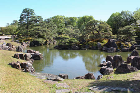 The pond of the Ninomaru Garden at Nij? Castle has a large pond with three islands and features numerous carefully placed stones and topiary pine trees in Kyoto, Japan Stock Photo