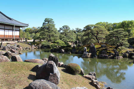 The pond of the Ninomaru Garden at Nijō Castle has a large pond with three islands and features numerous carefully placed stones and topiary pine trees in Kyoto, Japan