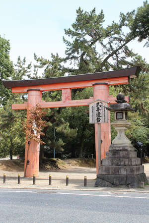 Japanese Torii Gate at Kasuga-taisha and a stone lantern in sunny spring day, Nara