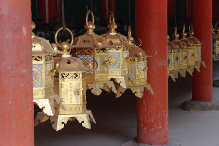 Row of gold ornate bronze lanterns in gilded as the famous point of Kasuga Grand Shrine in Nara, Japan