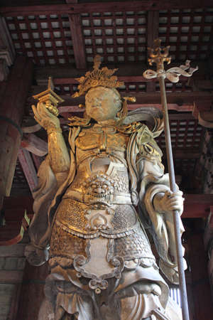 Bishamonten is the god of prosperity (symbolised by the treasure tower), the god of war and patron of warriors (symbolised by the defensive armour and offensive weapon). He brings good luck in both battle and defence at Todaiji Temple in Nara, Japan Editorial
