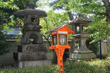 Antique stone lanterns and wood lantern at Yasaka Shrine in Kyoto, Japan