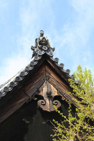 Antique Japanese ceramic roof tile decorated with swirling comma pattern called kawara and onigawara against blue sky near the Ishibe Michi in Kyoto, Japan Stock Photo