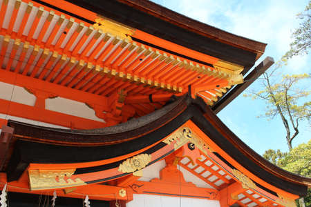 Roof detail of Yasaka shrine with vibrant orange and white colour and glided in Kyoto, Japan