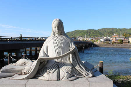 Tale of Genji Statue and Uji Bridge with the blue sky in Uji, Japan Editorial
