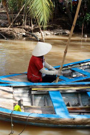 Vietnamese woman rowing a sampan (wooden boat) in Mekong River