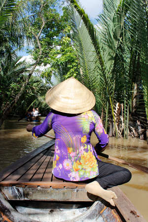 Vietnamese woman rowing a sampan (wooden boat) in Mekong River