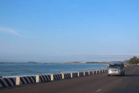 Landscape Of Mui Ne Bay with the fishing boats in the sea and van on the road