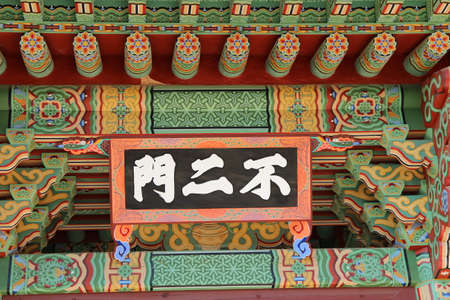 Korean traditional architecture detail of plaque with Chinese words as Bu Er Men (Burimun Gate) at Beomeosa Temple in Busan, South Korea