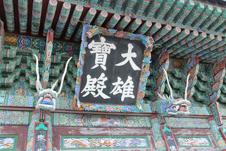 Korean traditional architecture entrance with dragons head sculpture and plaque of chinese words as Daeungjeon Main Hall at Haedong Yonggungsa Temple in Busan, South Korea