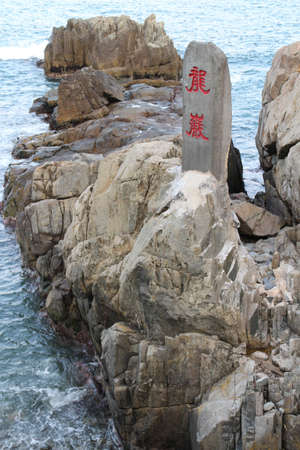 Rocky seaside of Haedong Yonggungsa Temple with a stone signage with the chinese calligraphy as Dragon Rocks in cloudy day, Busan, South Korea