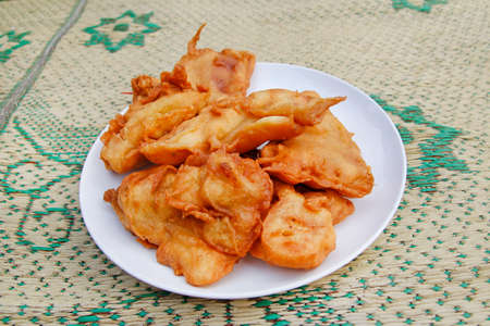 Pisang goreng (fried banana) in a plate on the straw mat at Yogyakarta, Indonesia Stock Photo