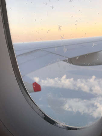 Dramatic cloudscape with the airplane's wing during sunrise from the airplane's window Banco de Imagens