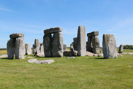 View of Stonehenge with green meadow and blue sky on a sunny day in Spring, United Kingdom