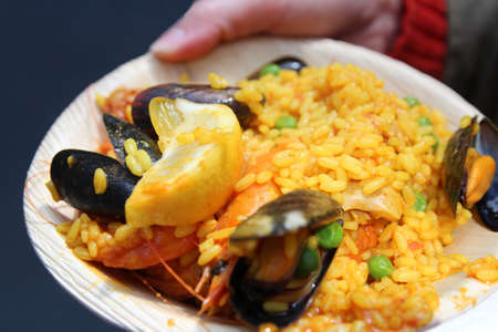 A hand holding the plate of seafood Paella in a plate at Borough Market, London, UK