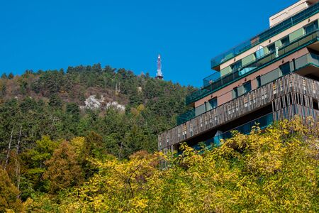 beautiful mountain landscape with forest consisting of many green and yellow trees, a glass building on the right and a blue sky Stock fotó