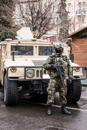 special operations: Fully equipped Romanian special operations soldier in front of an armored transport vehicle. Editorial