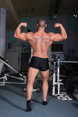young bodybuilder posing in the gym photo