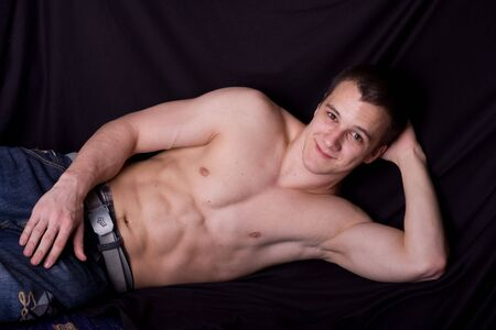 muscular man lying on bed photo
