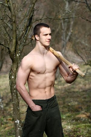 woodcutter: muscular woodcutter in a forest
