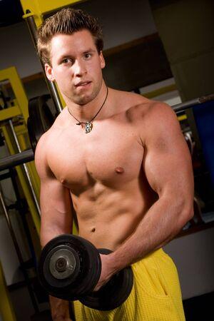bodybuilding boy: Bodybuilder training in the gym Stock Photo