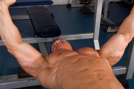 inddor: bodybuilder training in the gym -bench press