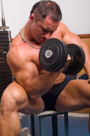 bodybuilder training: bodybuilder training his bicep in gym