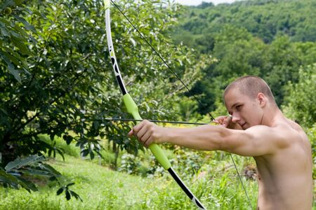 young muscular archer practising in a forest photo